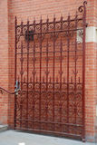Red Iron Gate Against Brick Wall. Red Iron Gate outdoors in front of brick wall Royalty Free Stock Photo