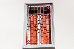 Red iron grating on grey square window Stock Image