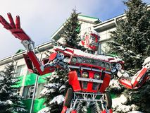 Red iron metal big strong dangerous fantastic, futuristic humanoid robot from a car with hands and head in winter royalty free stock image