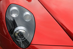 Red italian modern sports car headlamp. Sporty modern Italian supercar headlamp close up Royalty Free Stock Images