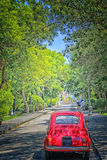 Red Italian runabout. Red vintage Italian runabout car in green park Stock Photos