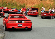 Red italian sports car rear view. Rear view Ferrari f355 with brake lights on in red among other Italian cars on mountain parking lot at Italian car event in stock image