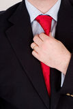A red ite. A business man in a blue suit, straightening his red tie Stock Photo