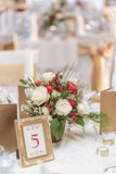 Red and ivory floral arrangement prepared for reception, wedding table with candle and setting, winter concept Stock Photos