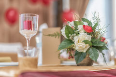 Red and ivory floral arrangement prepared for reception, wedding table with candle and setting, winter concept Stock Image