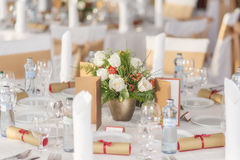 Red and ivory floral arrangement prepared for reception, wedding table with candle and setting, winter concept Royalty Free Stock Image