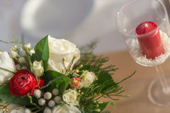 Red and ivory floral arrangement prepared for reception, wedding table with candle and setting, winter concept Stock Images