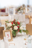 Red and ivory floral arrangement prepared for reception, wedding table with candle and setting, winter concept Stock Photo
