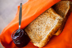 Red jam and toast. In orange servette Royalty Free Stock Images