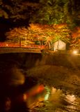 A red Japanese Bridge crossing a stream with light up red autumn tree royalty free stock photos