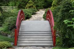 Red Japanese Garden Bridge. Connected to a stone walkway path over a small lake Royalty Free Stock Images