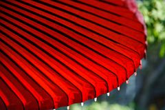 Red Japanese Umbrella. A red japanese umbrella on a green garden background Stock Images