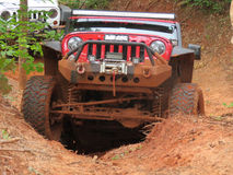 Red jeep attempts to climb a big hill off road Royalty Free Stock Photo