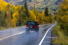 Red jeep drives Wet autumn road goes from Ouray to Silverton Col royalty free stock photos