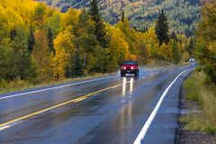Red jeep drives Wet autumn road goes from Ouray to Silverton Col stock photography