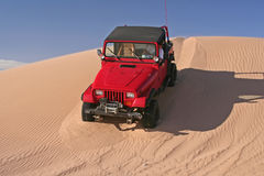 Red Jeep driving down a sand dune Stock Photography