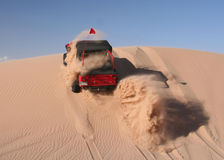 Red Jeep driving up sand dune Stock Image