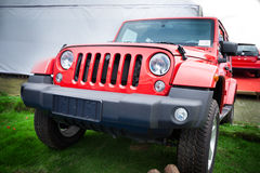 Red jeep. Front view of the 4-wheel drive red jeep on the grass royalty free stock images