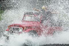 Red Jeep In High Speed Cross Water. 12/12/2017, Yogyakarta, Indonesia: Red jeep in high speed cross water. Domestic tourists enjoy the sensation of Lava Tour Stock Image