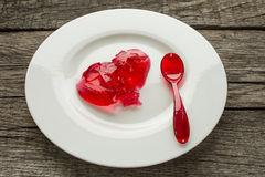 Red jello with spoon. On a plate Royalty Free Stock Photo