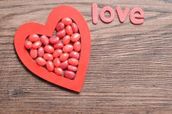 Red jelly beans displayed in a red heart shape with the word love. On a wooden background Stock Images