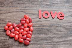 Red jelly beans with the word love. On a wooden background Stock Image