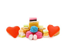 Red jelly hearts and mix of sweets. In love with sweets - red jelly hearts, caramel fudge, bonbons, vanilla toffee and marshmallow candy isolated on white. This stock photo