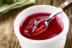 Red Jelly or Jello on Spoon. Eating red jelly or jello, spoonful of jelly on the top Selective Focus, Focus in the middle of the image Stock Photo