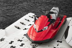 Red jet ski parked beside the sea. On black and white scene Royalty Free Stock Images