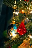 Red jewel Christmas ornament hanging among others on tree Stock Photo