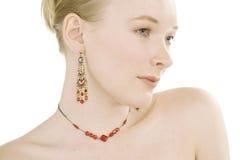 Red Jewelery. High key studio shot of beautiful fashion model wearing red jewelery stock image
