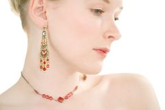 Red Jewelery. High key studio shot of beautiful fashion model wearing red jewelery stock photography
