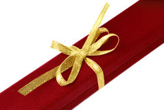 Red jewelry box with gold ribbon. Red velvet jewelry box tied by gold ribbon isolated Royalty Free Stock Image