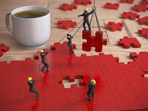 Red Jigsaw puzzle being built by teamwork of miniature people as. A great red jigsaw puzzle being built by a team of miniature people on a wood table next to a Royalty Free Stock Photography