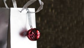 Red jingle bell on silver shopping bag Stock Images