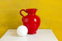 Red jug and white ball on table Royalty Free Stock Photography