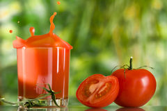 Red juice. View of nice red tomatoes and some glass of juice beside Stock Image