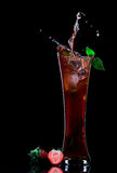 Red juice. View of strawberry juice splashing out of glass on black back Royalty Free Stock Photos