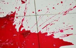 Red juice concentration splash on floor after bottle broken Royalty Free Stock Image