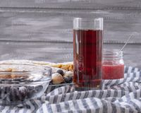 Red juice in a glass next to a bowl of cookies and a jar of jam, on a gray background stock images