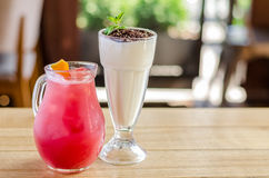 Red juice in a jug with lemon and a white cocktail in a glass with chocolate and mint on a wooden table, side view stock photo
