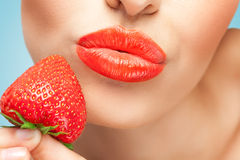 Red and juicy. A creative portrait of a sensual girl holding a red juicy strawberry near her tasty lips Royalty Free Stock Image