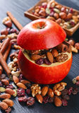 Red juicy apple with assorted nuts , raisins and cinnamon Stock Images
