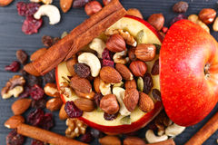 Red juicy apple with assorted nuts , raisins and cinnamon Stock Photography