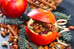 Red juicy apple with assorted nuts , raisins and cinnamon Royalty Free Stock Photography