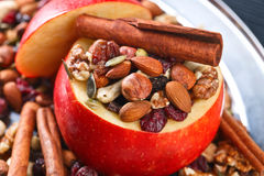 Red juicy apple with assorted nuts , raisins and cinnamon Royalty Free Stock Image