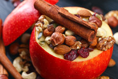 Red juicy apple with assorted nuts , raisins and cinnamon Stock Photo