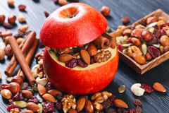 Red juicy apple with assorted nuts , raisins and cinnamon Royalty Free Stock Photos
