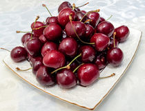 Red juicy Cherries on white plate Stock Images