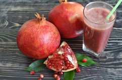 Red juicy fruit pomegranate and red smoothie in a transparent glass stock photo